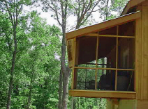 Screen porch at tree top level on hunting and fishing vacation cabin.