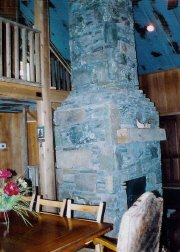 Massive stone fireplace makes this cozy cabin perfect for winter as well as summer vacations.